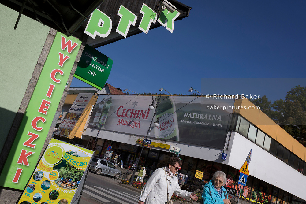 Elderly Polish shoppers walk past advertising signs, on 21st September 2019, in Szczawnica, Malopolska, Poland.