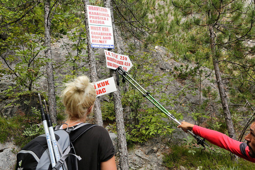 HIkers looking at trail and warning  signs, Čvrsnica mountain, Bosnia and Herzegovina.