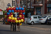 A balloon vendor is pushing his cart along the streets of Agra near the Taj Mahal.