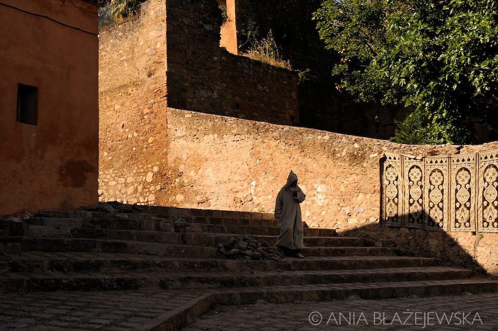 Morocco, Chefchaouen. Man in jellaba walking down the stairs near kasbah.