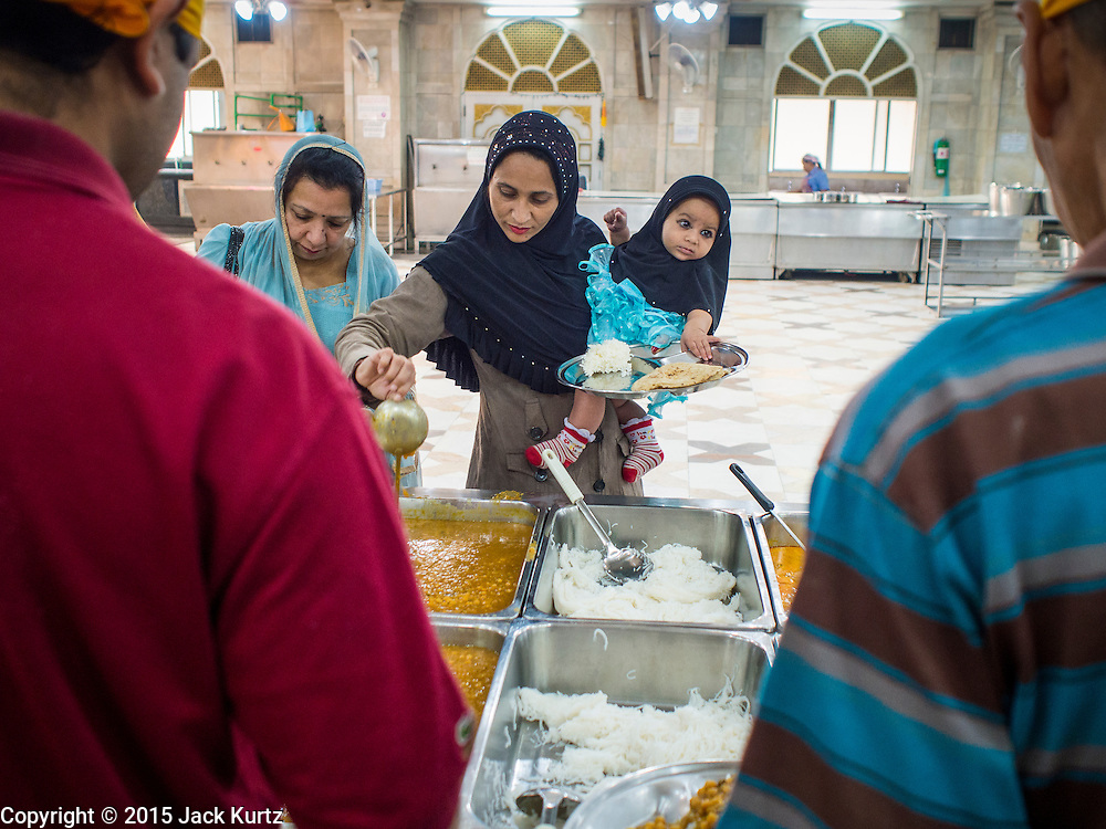 """08 FEBRUARY 2015  BANGKOK, THAILAND: A Muslim woman and her children gets curried vegetables during the community meal at the Sikh temple in Bangkok. Thailand has a small but influential Sikh community. Sikhs started coming to Thailand, then Siam, in the 1890s. There are now several thousand Thai-Indian Sikh families. The Sikh temple in Bangkok, Gurdwara Siri Guru Singh Sabha, was established in 1913. The current building, adjacent to the original Gurdwara (""""Gateway to the Guru""""), was built in 1979. The Sikh community serves a daily free vegetarian meal at the Gurdwara that is available to people of any faith and background.    PHOTO BY JACK KURTZ"""