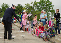 Bob Kennelly past commander of VFW Post 33 is greeted by a group of youngsters along the parade route from Main Street to Hesky Park in Meredith during Memorial Day services on Monday morning.  (Karen Bobotas/for the Laconia Daily Sun)