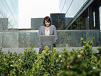 Mid adult businesswoman sitting outside office buildings using laptop