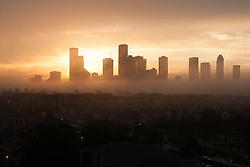 Sun setting behind the silhouetted Houston, Texas skyline.