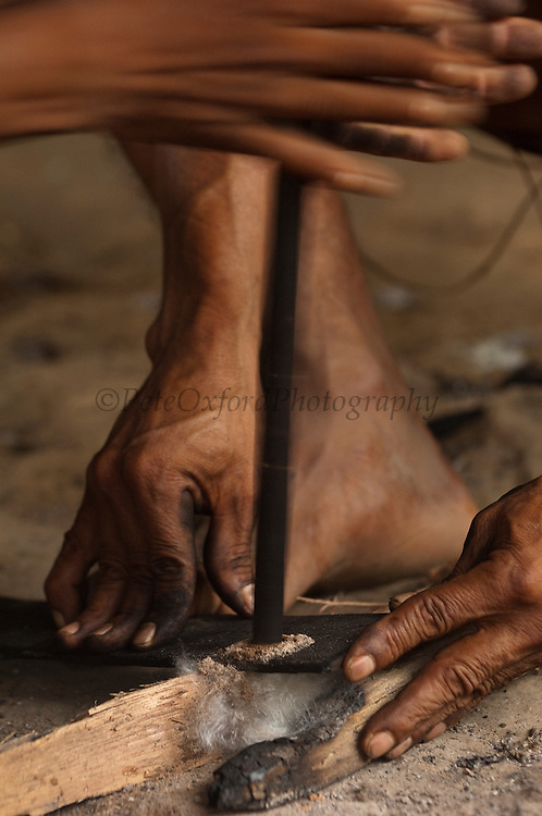 Huaorani Indians making fire. Gabaro Community. <br /> Amazon rainforest, ECUADOR.  South America<br /> Fire is traditionally made by rubbing a hard wood stick in a hole made in another hard wood base. Both woods having been previously hardened by using fire. Underneath the base is a wod of kapak wool - a natural product from the forest. This will ignite when the heat caused by the friction of the rubbing action is sufficient to set it alight. As soon as the first sparks and smoke appear in the kapok it is meticulously nurtured by blowing and adding tiny pieces of tinder until there is an active flame.<br /> <br /> This Indian tribe were basically uncontacted until 1956 when missionaries from the Summer Institute of Linguistics made contact with them. However there are still some groups from the tribe that remain uncontacted.  They are known as the Tagaeri. Traditionally these Indians were very hostile and killed many people who tried to enter into their territory. Their territory is in the Yasuni National Park which is now also being exploited for oil.