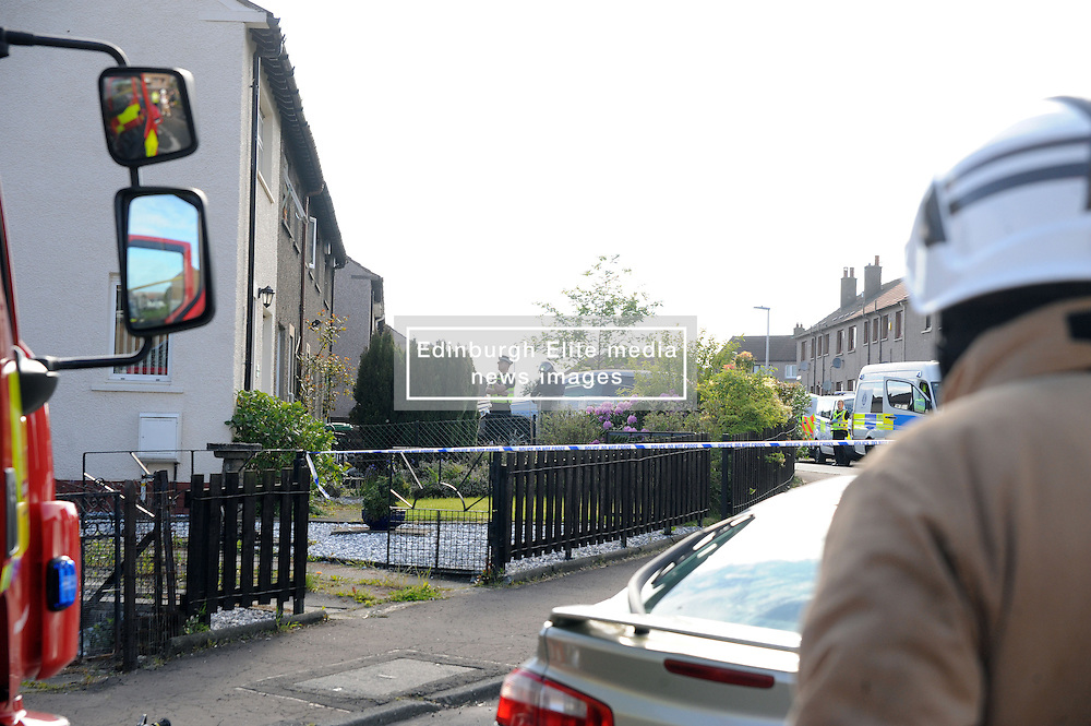 Police Scotland officers in riot gear and units from the local fire station attended a seige in a house in Lomond Crescent Dunfermline while neighbours look on from their windows<br />