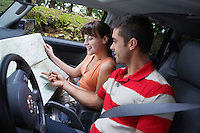 Couple observing map in car