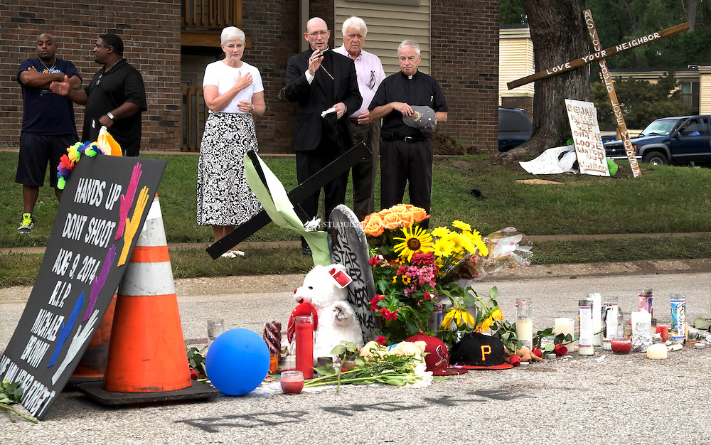 Bishop Edward M. Rice prayed at the memorial site for Michael Brown, whose shooting by a police office sparked civil unrest, looting and rioting in Ferguson. With Bishop Rice were Sister Cathy Doherty, SSND; Jim Kemner, a parishioner at Our Lady of Guadalupe; and Msgr. Jack Schuler, director of mission integration of Catholic Charities of St. Louis. The ministry of presence and prayer performed by clergy is having an effect on people on both sides of the police line. (Photo by Teak Phillips/St. Louis Review)