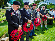 "11 NOVEMBER 2018 - KANCHANABURI, KANCHANABURI, THAILAND:  Veterans lay to wait wreaths during the Rememberance Day ceremony at the Kanchanaburi War Cemetery in Kanchanaburi, Thailand. Kanchanaburi is the location of the infamous ""Bridge On the River Kwai"" and was known for the ""Death Railway"" built by Japan during World War II using allied, principally British, Australian and Dutch, prisoners of war as slave labor. There are 6,982 people buried in the cemetery, including 5,000 Commonwealth soldiers and 1,800 Dutch soldiers. November 11, 2018 marked the 100th anniversary of the end of World War I, celebrated as Rememberance Day in the UK and the Commonwealth and Veterans' Day in the US.   PHOTO BY JACK KURTZ"