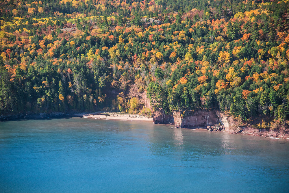 Aerial photography of the rugged Lake Superior shoreline north of Marquette, Michigan during fall color season. Areas shown include Little Presque Isle.