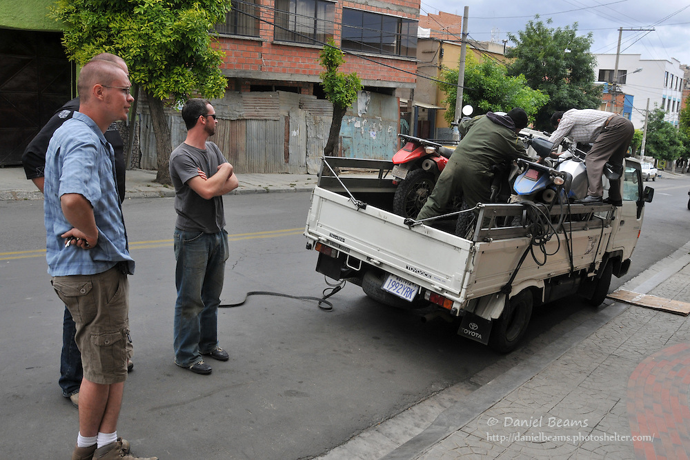 Loading motorcycles on flatbed truck in La Paz, Bolivia