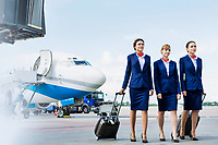 Photo of three confident flight attendants walking against airplane in airport