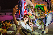 "19 JANUARY 2014 - BANGKOK, THAILAND:  A member of the audience takes a ""selfie"" with his iPhone with a performer during a mor lam show in Khlong Tan Market in Bangkok. Mor Lam is a traditional Lao form of song in Laos and Isan (northeast Thailand). It is sometimes compared to American country music, song usually revolve around unrequited love, mor lam and the complexities of rural life. Mor Lam shows are an important part of festivals and fairs in rural Thailand. Mor lam has become very popular in Isan migrant communities in Bangkok. Once performed by bands and singers, live performances are now spectacles, involving several singers, a dance troupe and comedians. The dancers (or hang khreuang) in particular often wear fancy costumes, and singers go through several costume changes in the course of a performance. Prathom Bunteung Silp is one of the best known Mor Lam troupes in Thailand with more than 250 performers and a total crew of almost 300 people. The troupe has been performing for more 55 years. It forms every August and performs through June then breaks for the rainy season.              PHOTO BY JACK KURTZ"