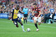 21.04.2013 Sydney, Australia. Mariners forward Bernie Ibini-Isei  and Wanderers striker Mark Bridge in action during the Hyundai A League grand final game between Western Sydney Wanderers FC and Central Coast Mariners FC from the Allianz Stadium.Central Coast Mariners won 2-0.