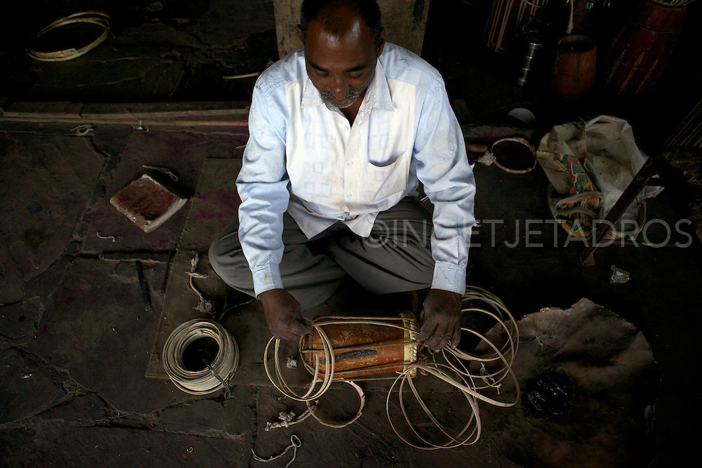 A drum repairshop in Gujarat. Once a week these 'drum repairers' will come to this local market and repair drums. Skin is available for sale and people can choose the skin they like and a skinner will prepare the skin to fit on a drum of choice. Gujarat, India