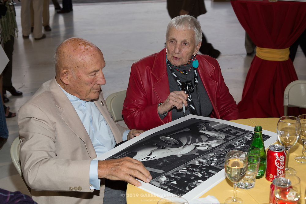 Sir Stirling Moss and Denise McCluggage signing autographs.