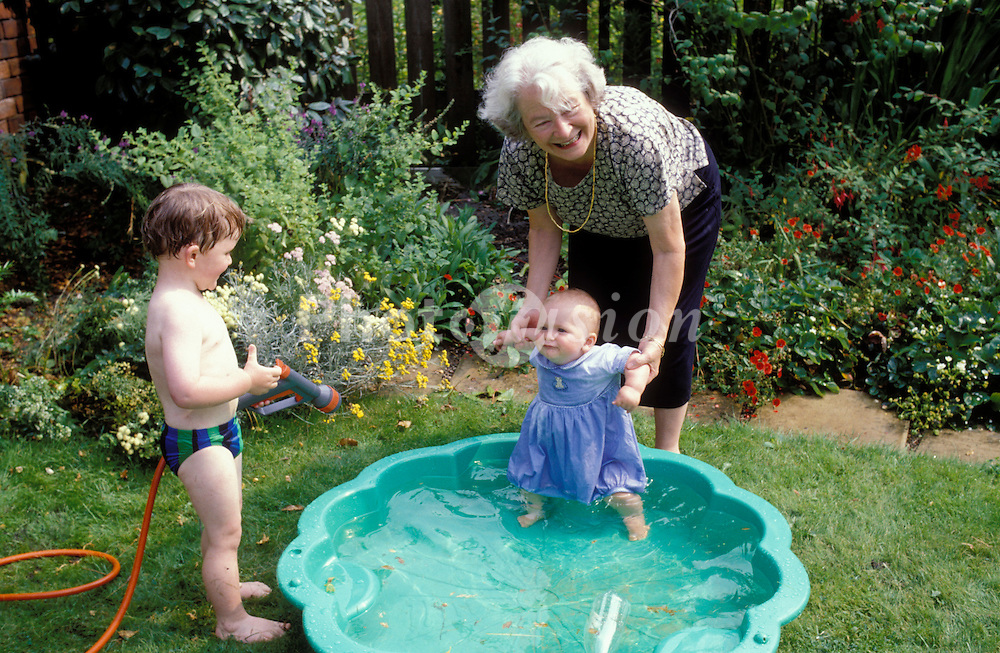 Grandmother playing with her grandchildren in paddling pool in the garden in summer; UK