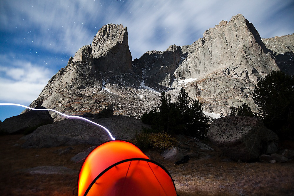 Moonlight illuminates War Bonnet and Warrior Peaks above a glowing tent in the Cirque of the Towers, Popo Agie Wilderness, Wind River Range, Wyoming.