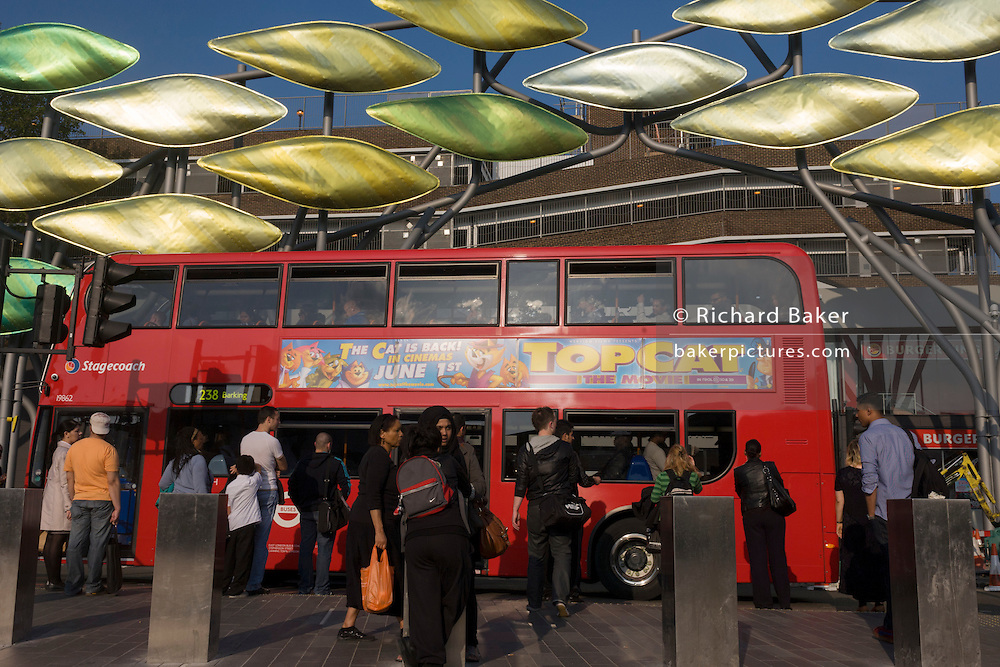 Red London double-decker bus and commuters beneath the new kinetic sculpture at Stratford Centre 'The Shoal' at the Stratford Centre, east London, is made up of around 100 titanium clad 'leaves' mounted between 15 and 19 metres high on metal posts. Worth £13.5m, the Shoal is part of The Stratford Town Centre Public Realm Project, designed and manufacturered using 3D technology.