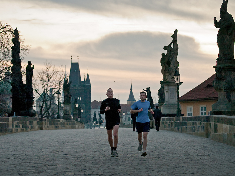 Two runners passing early morning Prague Charles Bridge. Charles Bridge is one of the oldest and certainly one of the most beautiful stonebridges in Europe, this ancient artery across the Vltava river links Pragues Lesser Town with the Old Town on the right bank.