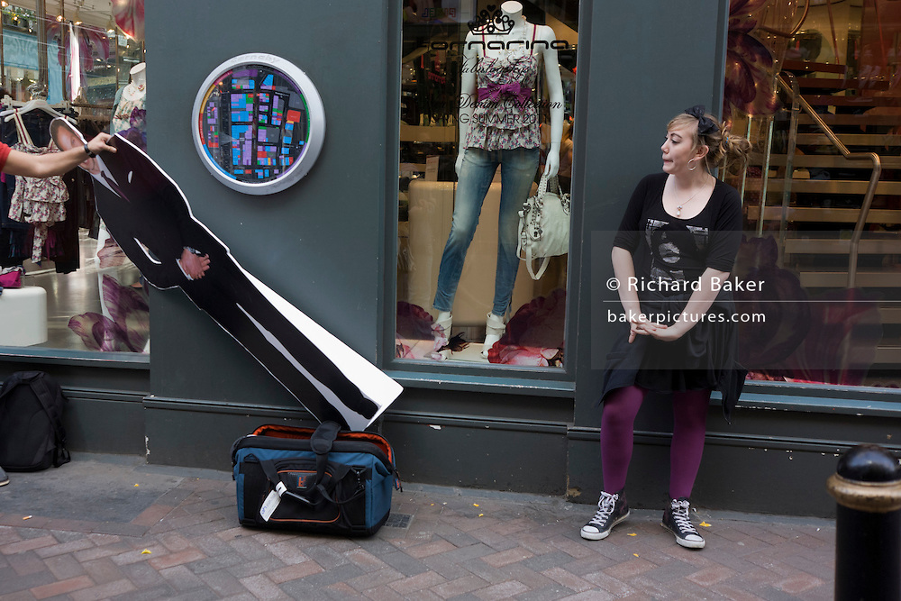 Woman waits for interview with life-size carboard cut-out of Prince William in a London street during filming of vox pop.
