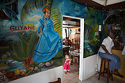 Holding her doll, a young white child wearing a pink dress explores the Délice Restaurant in old Kourou, French Guiana, South America. The daughter of French parents who are in this French-administered colony in connection with the nearby European Space Agency (ESA). The girl is confident enough to leave her parents' side and appear in an open doorway. On the other side of the wall is a giant brightly-painted mural depicting a more traditional side of life in this tropical country. The word Guyane is the French name for Guiana. A female in national costume stands near a palm tree, local produce and vegetation. Meanwhile a dark-skinned Creole man sits on a stool smoking a cigarette chatting to unseen friends - a barfly occupying his usual lunchtime seat. It is a scene of internationalism, cross-culture and youth versus old age. .
