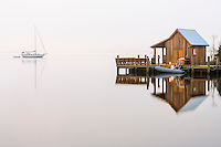 Boat shed and reflection in the fog.