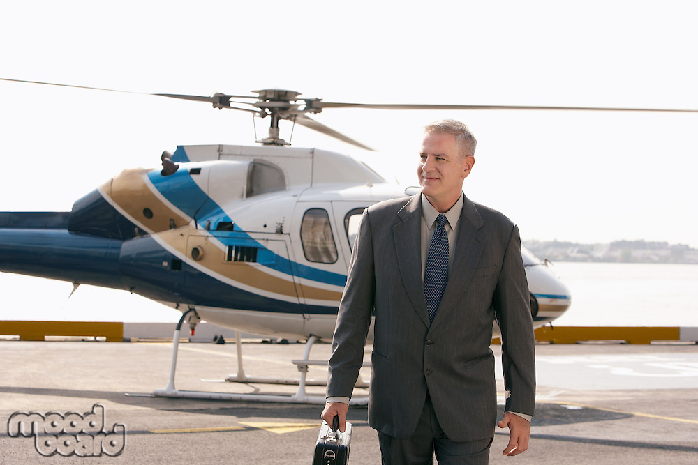 Businessman arriving on helicopter pad