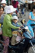 Rach Gia. Mother and child on a motorbike.