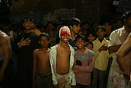 A Shiite Muslim boy smiles after flagelating himself with razor blades during a Muharram procession in New Delhi, India, Tuesday, March 2, 2004. Muharram is a month of mourning when Shiite Muslims recall the seventh-century death of Hussain, grandson of Prophet Mohammad.