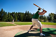 David Johnson, left, serves up some batting practice to his younger brother Tim on Wednesday afternoon at McEuen Park, taking advantage of the nice weather and available fields.