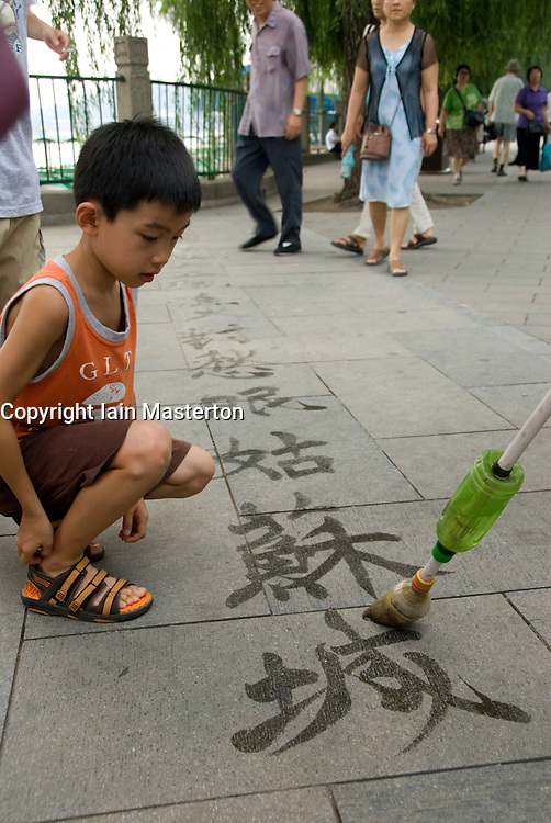 Boy watching man writing calligraphy on ground using water and brushes in park in Beijing China