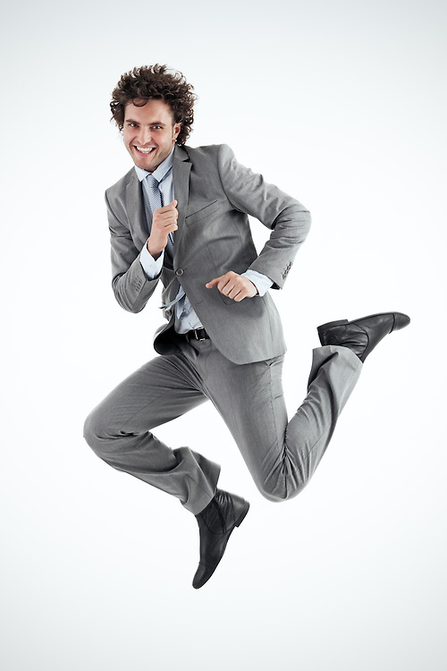 Young businessman excitedly jumps into the air in celebration. Vertical shot. Looking at camera.