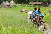 Vaccinator Bala Diakite and nurse Maba N'Djim ride a motorcycle as they head to the village of Banankoro, Mali to provide outreach health services on Saturday August 28, 2010. They visit the village once a month to provide services such as vaccination, prenatal counseling, and nutrition monitoring.