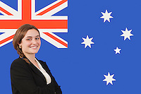 Portrait of young businesswoman smiling over Australian flag