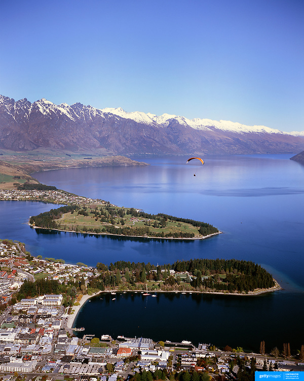 A paraglider flies above Queenstown, New Zealand, with the snow capped Remarkables mountain range providing a stunning backdrop. Queenstown is nestled on the shores of the crystal clear waters of Lake Wakatipu in the Central Otago region of the South Island of New Zealand. Queenstown is New Zealand's premier tourist destination providing an abundance of year round outdoor activities for both young and old. Queenstown, Central Otago, South Island, New Zealand. Photo Tim Clayton.