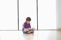 Boy (7-9) sitting on floor playing handheld game