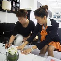 CHENGDU, 10/17/2012 :  Geschaeftsfrau Yang Xi, 37, laesst sich den Vertrag fuer den Kauf ihres neuen Autos   von einer Audimitarbeiterin erklaeren.
