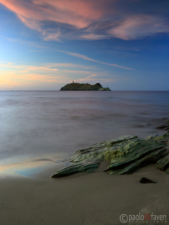 A view at sunset of the small island of Giraglia, from the beach of Barcaggio on the very tip of Cap Corse in Corsica, France.