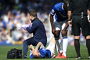 Everton defender Lucas Digne (12) lies injured as the physio signals to the bench that his game is over  during the Premier League match between Everton and Manchester United at Goodison Park, Liverpool, England on 21 April 2019.
