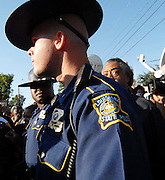 Reverend Al Sharpton, right, peeks over the shoulder of a Louisiana State Police officer as he and other demonstrators march from the LaSalle parish courthouse to Jena High School, Thursday, Sept. 20, 2007, in Jena, Louisiana, U.S. The two-lane road leading to Jena was jammed with traffic today as thousands of people gathered to support black teenagers who had been charged with attempted murder in the beating of a white classmate. (Photo/Suzi Altman)