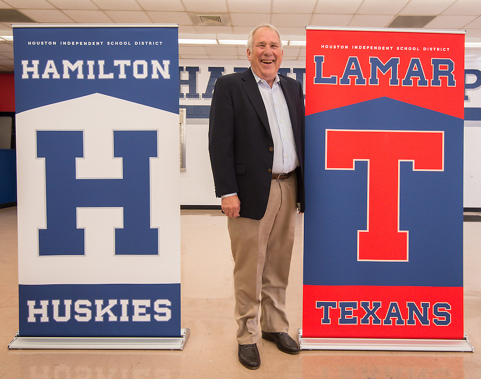 Head football coach Tom Nolan poses for a photograph next to a Lamar High School banner following the announcement of new mascot names for Lamar, Westbury High School, Welch Middle School and Hamilton Middle Schhool at Hamilton, April 15, 2014.