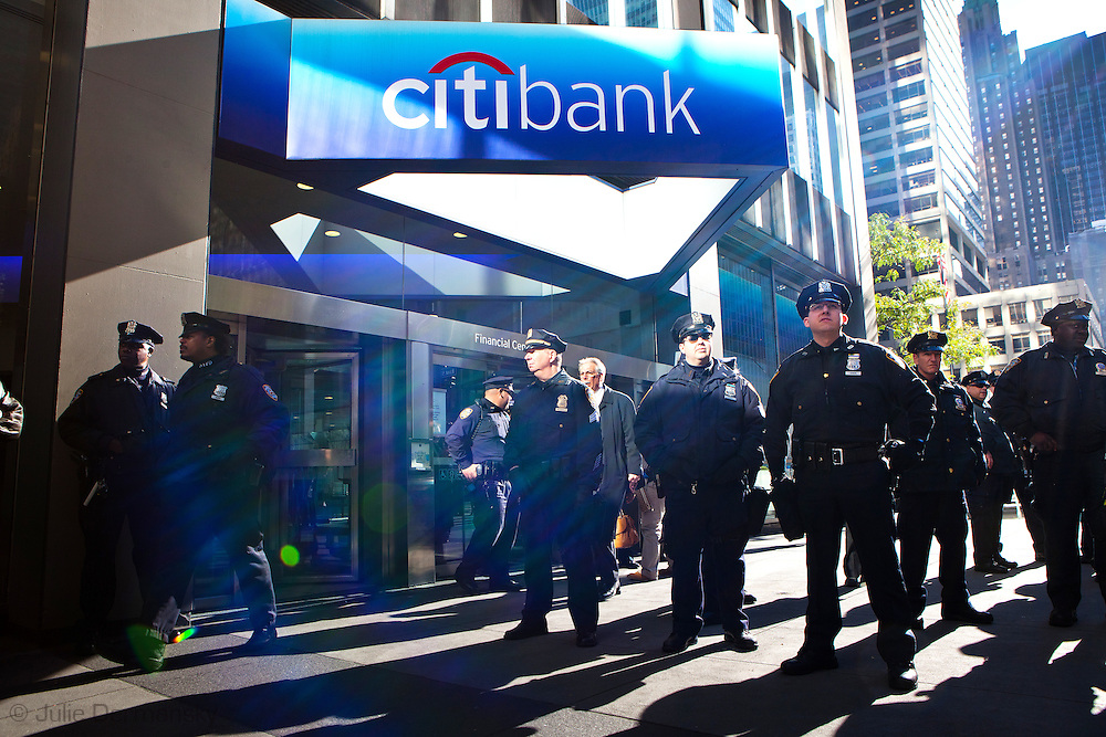 New York, NY- October 28th, members of the NYPD guard the entrance to Citibank as protesters participating in the Occupy Wall Street movement protest out front. Hundreds of protesters marched to headquarters of Bank of America, Morgan Stanley, Wells Fargo, Citigroup and JP Morgan Chase to delivers 6000 letters from unhappy bank customers.