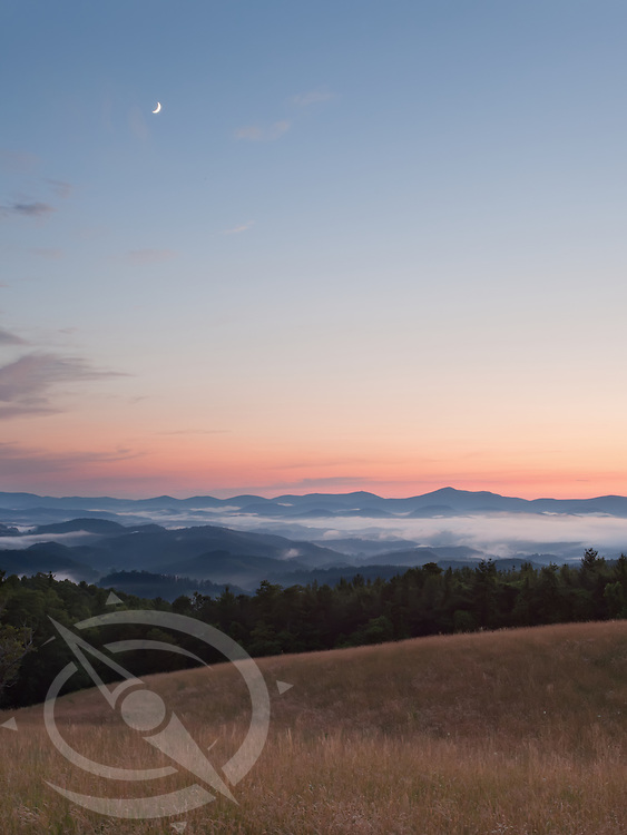 The moon starts setting early as the sun fades on the horizon of the Blue Ridge Mountains. Blue Ridge Parkway near E.B. Jeffress park, North Carolina