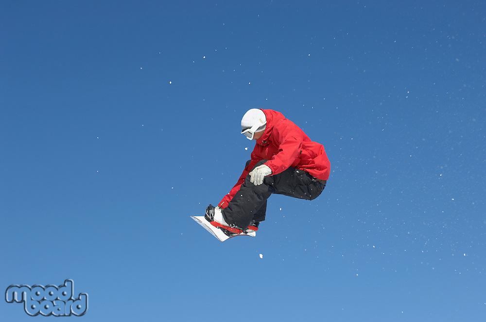 Teenage snowboarder jumping