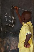 Student writes on blackboard in a classroom  at Pope John.s Catholic Junior High School, northern Ghana.