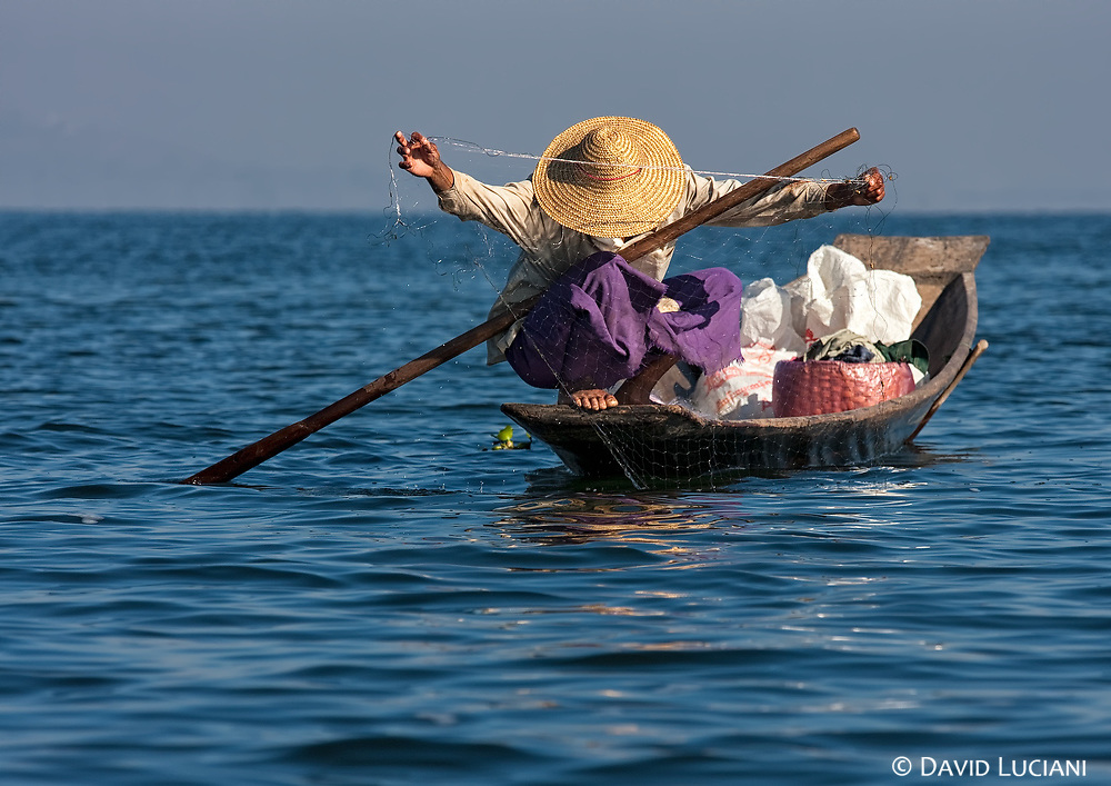 A man is spreading out his net to catch fishes.