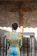 A Mexican Matador stops to pray at a small chapel before entering the bull ring for the bullfights at the Plaza de Toros in San Miguel de Allende, Mexico.