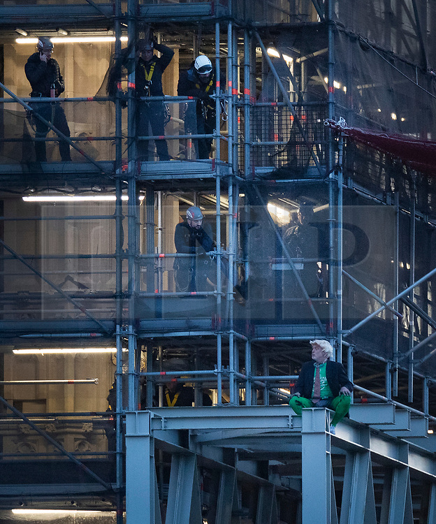 © Licensed to London News Pictures. 18/10/2019. London, UK. Police (top) talk to a man sitting on scaffolding surrounding Big Ben. He is believed to be part of an Extinction Rebellion protest. Photo credit: Peter Macdiarmid/LNP