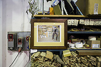 SOVERIA MANNELLI, ITALY - 16 NOVEMBER 2016: A photograpg of Camillo Sirianni (who passed away in 2007), is seen here in the warehouse of Camillo Sirianni, a school furniture manifacturer in Soveria Mannelli, Italy, on November 16th 2016.<br /> <br /> Camillo Sirianni is a third generation family business that started as a family mechanized carpentry in 1909 and transformed into a leading school furniture manufacturer. In a high-tech warehouse in the outskirts of Soveria Mannelli, they assemble thousands of Calabrian beechwooden, colorful desks, benches, closets and other accessories that are later shipped to many corners of the globe, from the United Kingdom to the Emirates, from central America to Polynesia.<br /> <br /> Soveria Mannelli is a mountain-top village in the southern region of Calabria that counts 3,070 inhabitants. The town was a strategic outpost until the 1970s, when the main artery road from Naples area to Italy's south-western tip, Reggio Calabria went through the town. But once the government started building a motorway miles away, it was cut out from the fastest communications and from the most ambitious plans to develop Italy's South. Instead of despairing, residents benefited of the geographical disadvantage to keep away the mafia infiltrations, and started creating solid businesses thanks to its administrative stability, its forward-thinking mayors and a vibrant entrepreneurship numbering a national, medium-sized publishing house, a leading school furniture manufacturer and an ancient woolen mill.